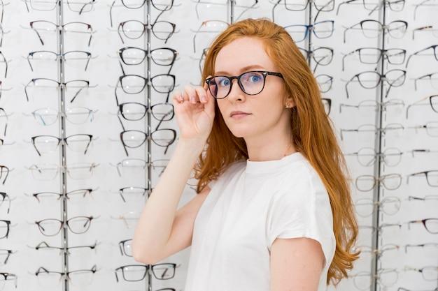 Eyeglasses красивой молодой женщины нося смотря камеру в магазине оптика Бесплатные Фотографии