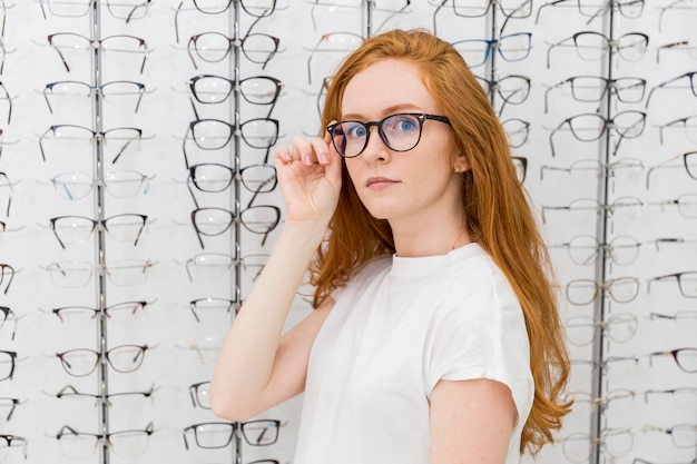 Beautiful young woman wearing eyeglasses looking at camera in optician shop Free Photo