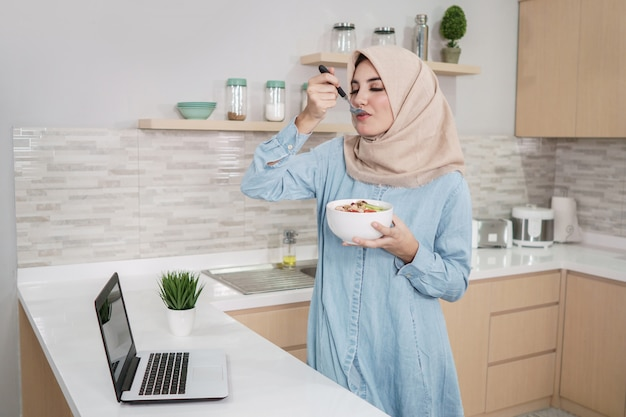 Beautiful young woman wearing hijab eating a bowl of granola wit Premium Photo