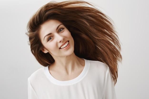 아름 다운 젊은 여자 채찍 머리와 미소. 헤어 케어 개념 무료 사진