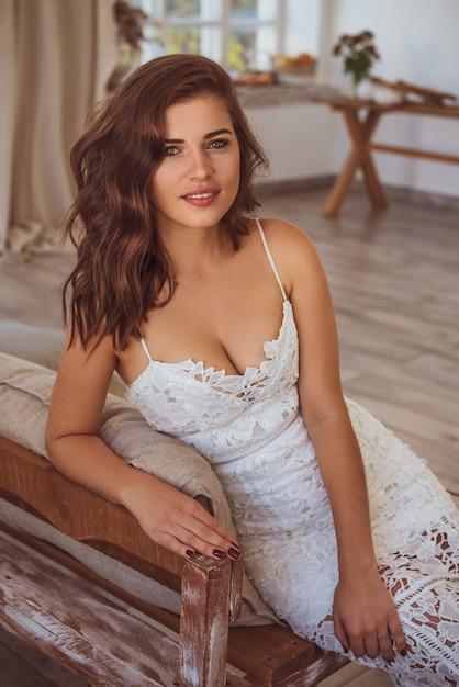 Beautiful young woman in white dress smiling toning photo Premium Photo