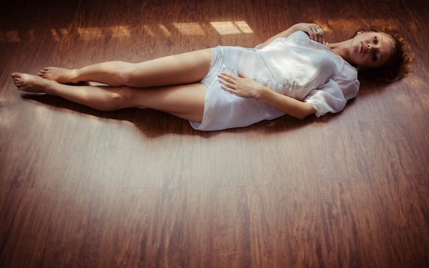 Beautiful young woman in white nightie lying on the floor Free Photo