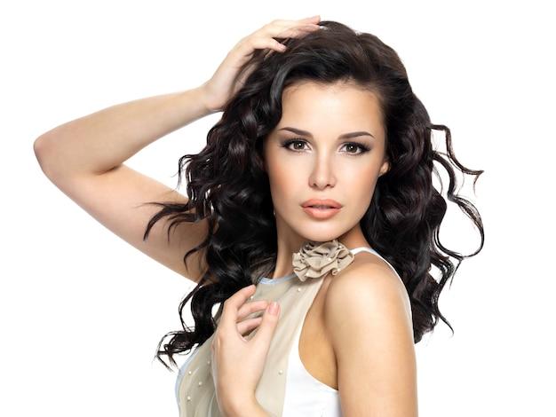 아름다움 긴 곱슬 머리를 가진 아름 다운 젊은 여자. 흰색 배경에 고립 된 패션 모델 초상화 무료 사진