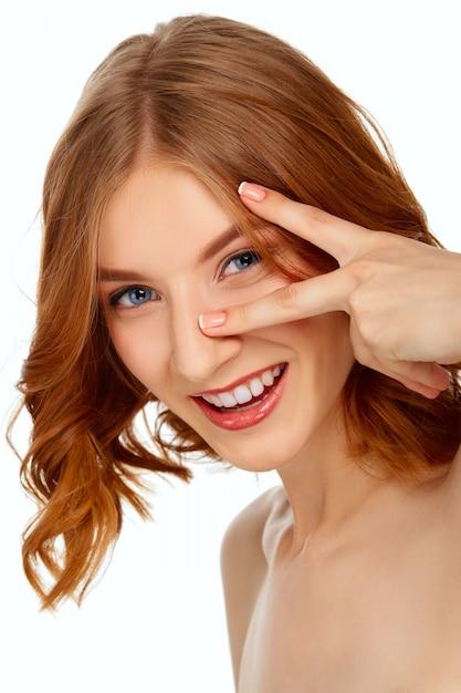 Красивая молодая женщина с голубыми глазами и красными губами показывает два пальца. Premium Фотографии