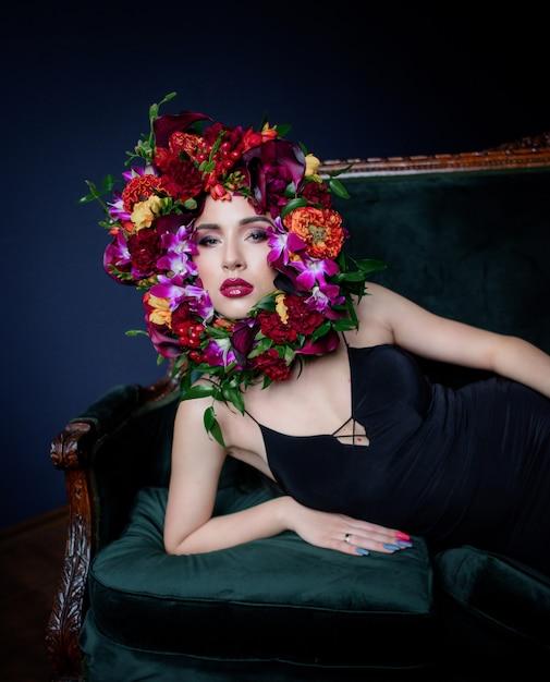 밝은 화장 아름 다운 젊은 여자는 녹색 소파, 어두운 파란색 배경에 화려한 신선한 꽃으로 둘러싸인 얼굴에 누워있다 무료 사진