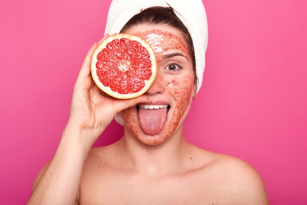 Beautiful young woman with bright scrub on her face holds half of rape grapefruit in one hand, sticks out her tongue, having white towel on her head, looks fresh and delighted. skin care concept. Free Photo