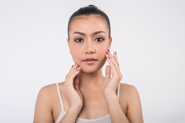 Beautiful young woman with clean fresh skin touch own face Free Photo