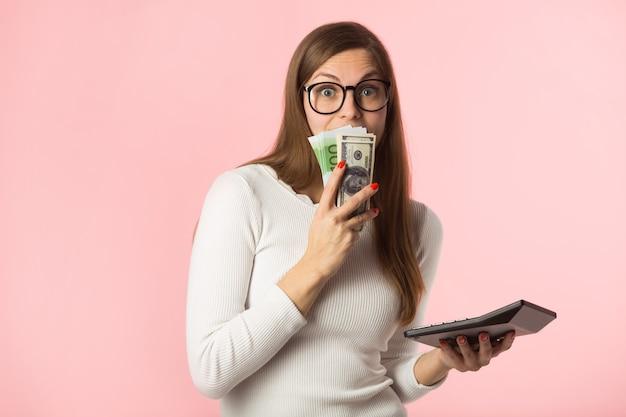 ピンクの背景にユーロとドルの美しい若い女性 Premium写真