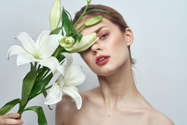 Красивая молодая женщина с цветком позирует в студии на светлой стене, романтическое нежное изображение, женский портрет Premium Фотографии