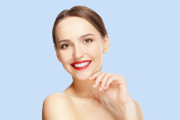 Beautiful young woman with fresh skin and red lips looking straight and demonstraiting healthy teeth. Premium Photo