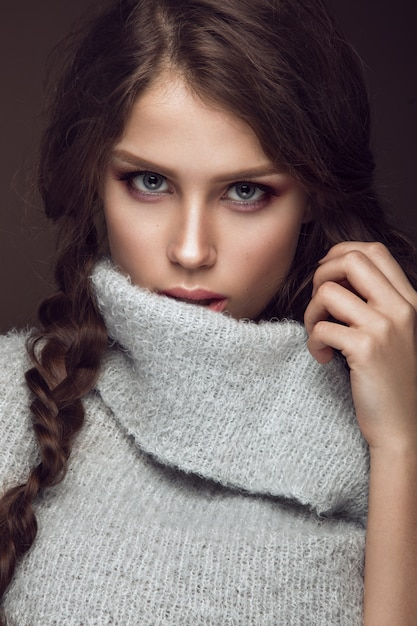 Beautiful young woman with gentle make-up in warm sweater and long straight hair Premium Photo