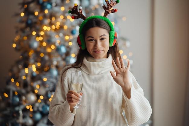 집에서 샴페인 한 잔과 아름 다운 젊은 여자. 크리스마스 축하 무료 사진