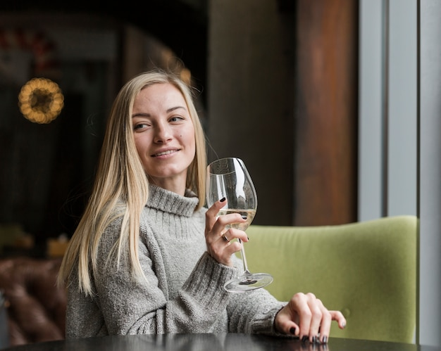 Beautiful young woman with glass of wine looking away Free Photo