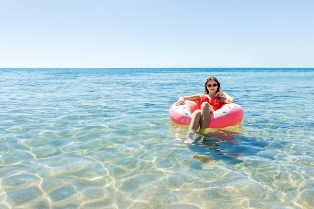 Beautiful young woman with inflatable donut in the sea Premium Photo