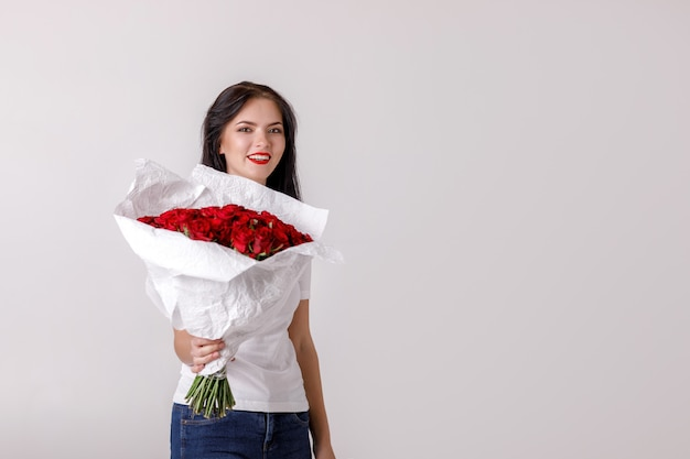 Beautiful young woman with a large bouquet of red roses Premium Photo