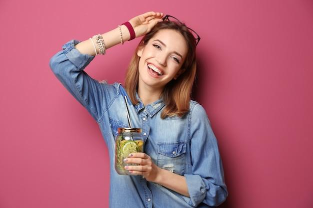 색상 배경에 레모네이드와 아름 다운 젊은 여자 프리미엄 사진