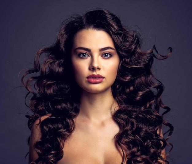 긴 곱슬 갈색 머리와 연기가 자욱한 눈 화장과 아름 다운 젊은 여자. 물결 모양의 헤어 스타일로 섹시하고 화려한 갈색 머리 소녀. 매력적인 여성의 초상화입니다. 패션 모델. 무료 사진