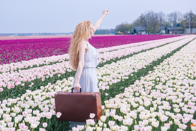 Beautiful young woman with long red hair wearing in white dress standing with luggage on colorful tulip field. Premium Photo