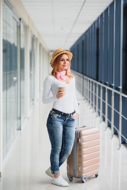 空港で荷物を持つ美しい若い女性 Premium写真
