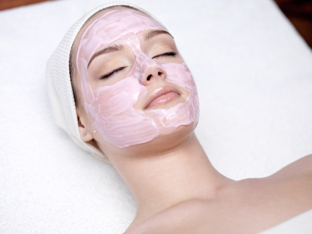 Beautiful young woman with pink facial mask in spa salon - indoors Free Photo