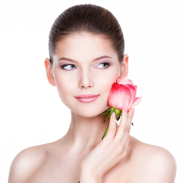 Beautiful young woman with pink rose. beauty treatment concept. portrait over white wall. Free Photo