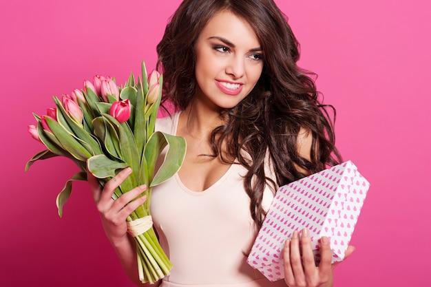 Красивая молодая женщина с весенним букетом и подарочной коробкой Бесплатные Фотографии