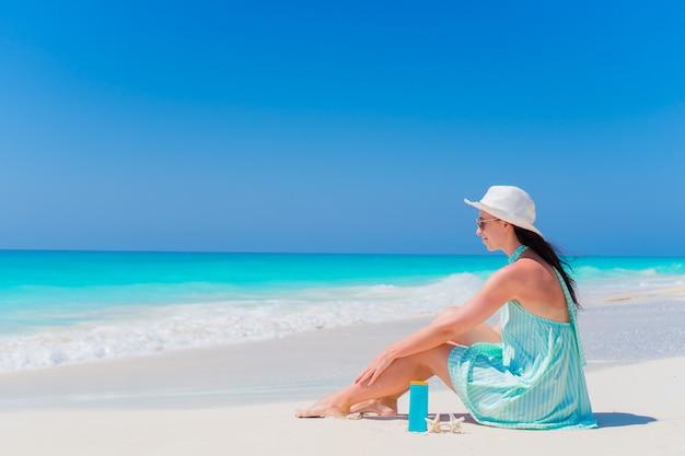 Beautiful young woman with suncream lying on tropical beach Premium Photo