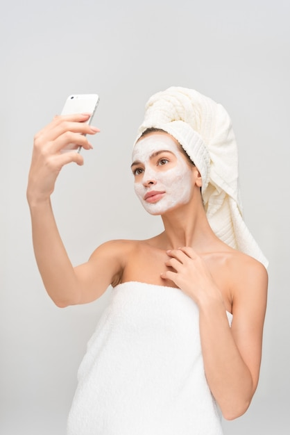 Beautiful young woman with white clay facial mask Premium Photo