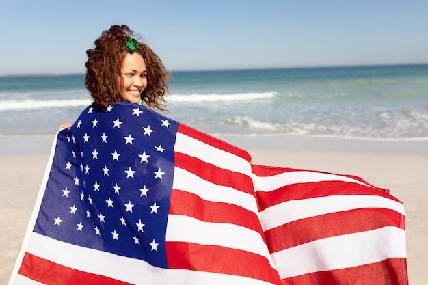 Beautiful young woman wrapped in american flag looking at camera on beach in the sunshine Free Photo