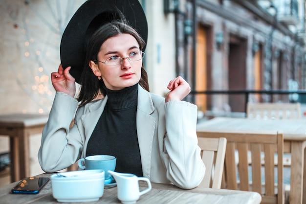 レストランでお茶を飲む美しい若い女性 Premium写真