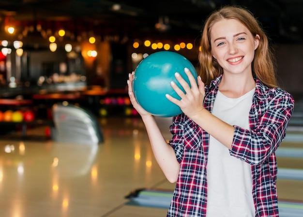 Belle giovani donne che tengono una palla da bowling Foto Gratuite