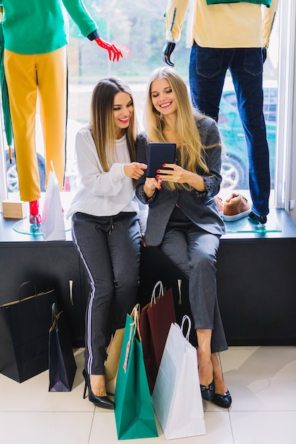2c1214443 Beautiful young women looking at digital tablet with colorful shopping bags  in the clothes store Free