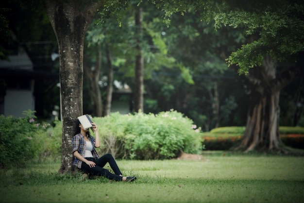 Beautiful young women reading a book in the park outdoor Free Photo