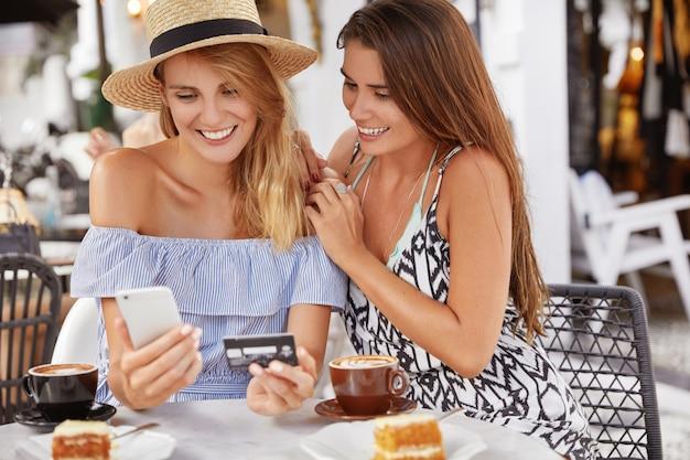 Belle giovani donne turisti trascorrono le vacanze estive all'estero, prenotano biglietti online con smartphone e tessera di plastica, trascorrono il tempo libero, si siedono insieme al bar, bevono caffè espresso o latte. Foto Gratuite