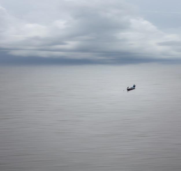 부드러운 바다와 맑은 하늘, 모션 블러 효과와 미니멀리즘에서 보트에 어부의 장거리와 Beautifull 자연. 프리미엄 사진