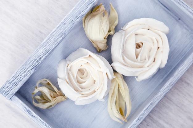 Красиво оформленный десерт. белая безе в форме цветов на деревянной синей коробке на столе. низкокалорийная сладость. яблочный зефир. вид сверху. Premium Фотографии
