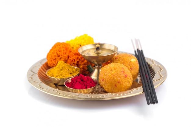 Beautifully decorated pooja thali for festival celebration to worship, haldi or turmeric powder and kumkum, flowers, scented sticks in brass plate, hindu puja thali Premium Photo