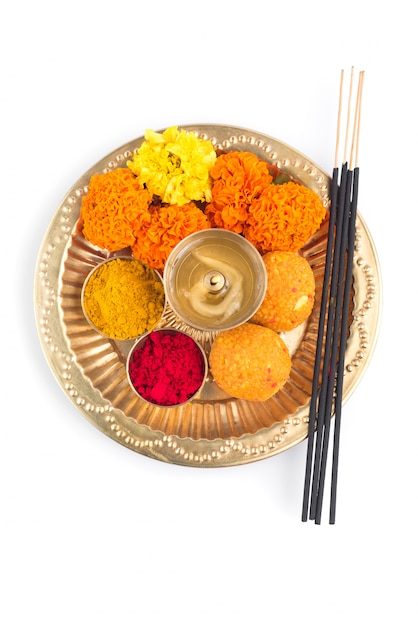 Beautifully decorated pooja thali for festival celebration to worship, haldi or turmeric powder and kumkum, flowers, scented sticks in brass plate, hindu puja thali Premium Photo