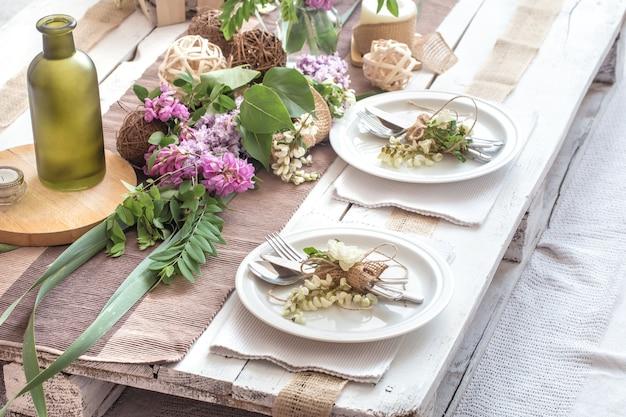 モダンなカトラリー、弓、ガラス、キャンドル、ギフトを備えた休日のための美しくエレガントな装飾が施されたテーブル 無料写真