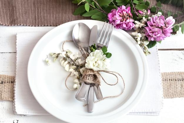 春の花と緑の休日のための美しくエレガントな装飾が施されたテーブル-結婚式やバレンタインの日、モダンなカトラリー、弓、ガラス、キャンドル、ギフト、水平、クローズアップ、トーン 無料写真