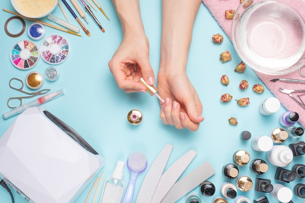 Beautifully manicured nails on the desktop with tools for manicure. care about the nails Premium Photo