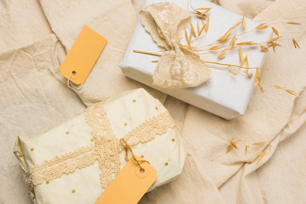 Beautifully wrapped gift boxes with tags on textured fabric Free Photo