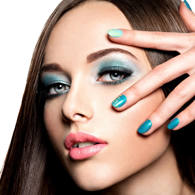 Beautiul fashion woman with turquoise make-up and nails  - on white wall Free Photo
