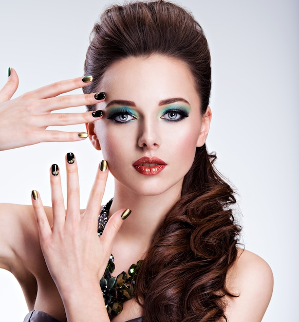 Beautiul woman with green make-up and creative color of nails Free Photo