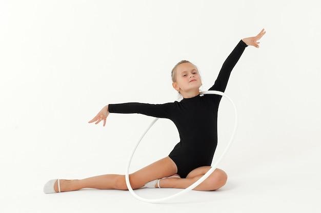 Красавица-акробат занимается гимнастической йогой, изолированной на белом пространстве Premium Фотографии