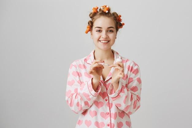 美しさとファッションのコンセプトです。ヘアカーラーとマニキュアを適用するパジャマの女の子 無料写真