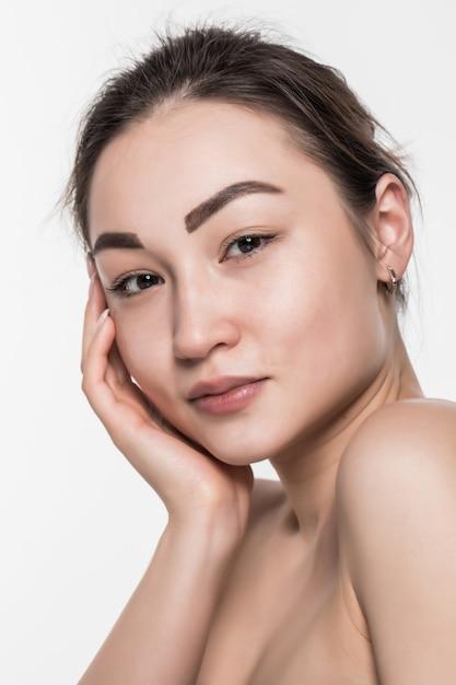 白い壁に分離された清潔でさわやかな肌を持つ美容アジア女性。 無料写真