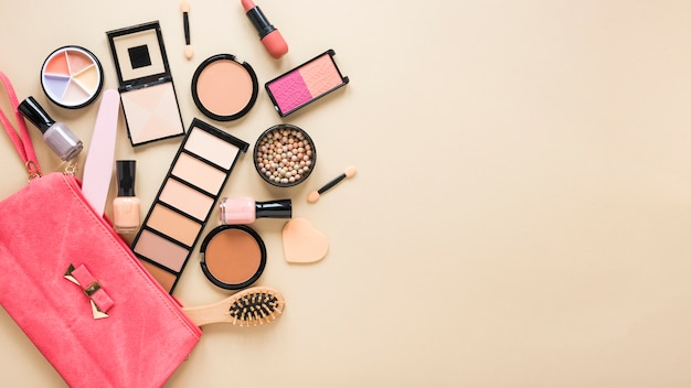 Beauty bag with facial powders and eye shadows on table Free Photo