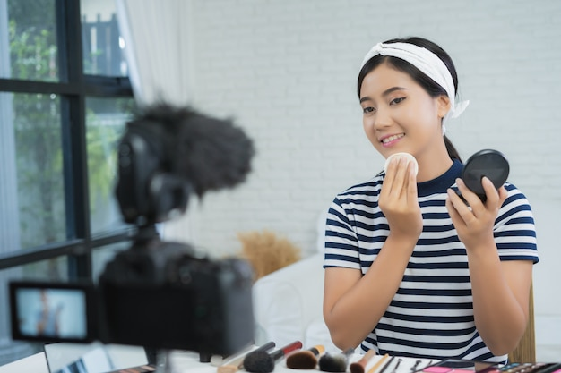 Beauty blogger present beauty cosmetics while sitting in front camera for recording video Free Photo