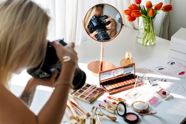 Beauty blogger taking photo of cosmetics Premium Photo